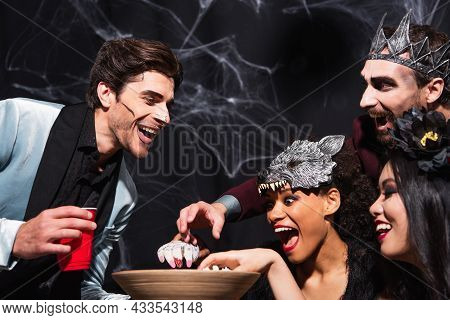 Astonished Multiethnic Friends Eating Popcorn During Halloween Party On Black