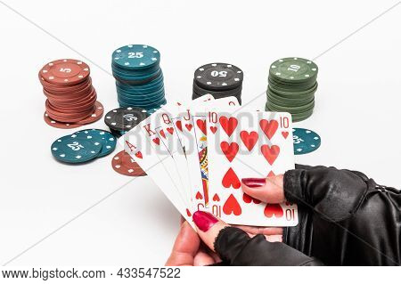 Female Hands In Gloves Hold Playing Cards With A Royal Flush Combination. The Game Of Poker.