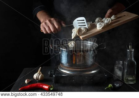 The Chef Cooks Meat Dumplings In A Saucepan In The Restaurant Kitchen. Close-up Of The Hands Of Cook