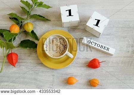 Calendar For October 11 : The Name Of The Month In English, Cubes With The Number 11, A Yellow Cup W