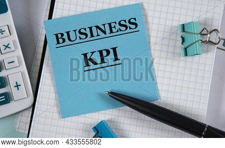 Business Kpi - Word On A Blue Piece Of Paper Against The Background Of A Notebook, Calculator And Pe