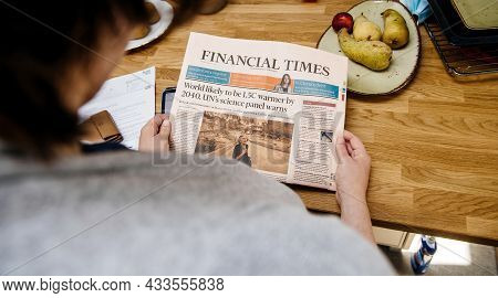Paris, France - Aug 12, 2021: Woman Reading In The Kitchen Early In The Morning Financial Times News
