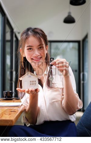 Smiling Young Woman Holding House Model And House Key. Real Estate Investment And Insurance Concept