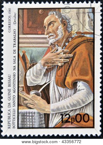 stamp printed in Guinea-Bissau shows St. Augustine in the work room by Botticelli