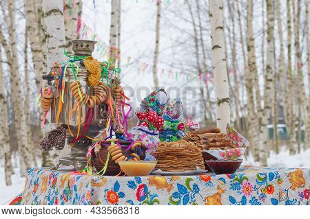 Festive Decor For Maslenitsa On The Table: Pancakes, Bagels, A Samovar, A Doll With Ribbons. Russian