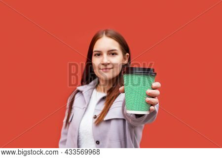 Charming Young Caucasian Woman Holding Disposable Blue Coffee Cup. Focus On Cup And Hand. Drinking C