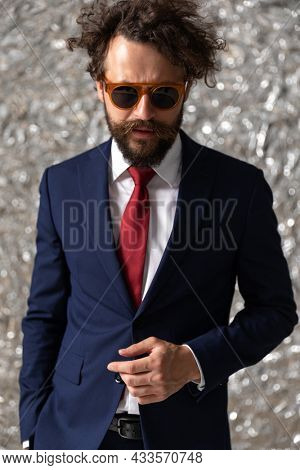 cool sexy businessman holding one hand in pocket and the other one loose against staniol background