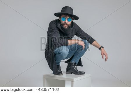 sexy fashion model posing with tough attitude and squatting against gray background