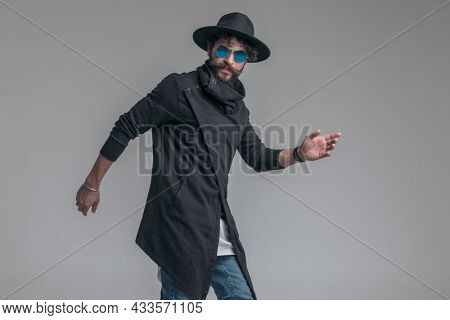sexy fashion model striking a pose and wearing sunglasses and a hat on gray background