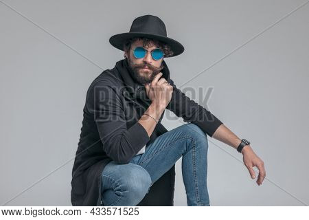 squatted casual man posing with attitude, touching his chin and wearing sunglasses on gray background