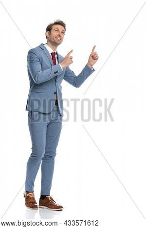 young businessman in blue suit looking up and pointing finger up, looking up and walking isolated on white background in studio