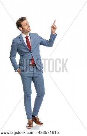 elegant businessman in blue suit looking to side, holding hand in pocket, pointing finger up and side and smiling on white background in studio