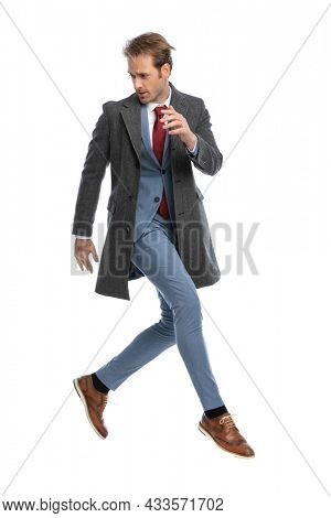 full body picture of dynmaic businessman in suit with grey jacket looking to side, holding arm in fashion pose and jumping in the air on white background in studio