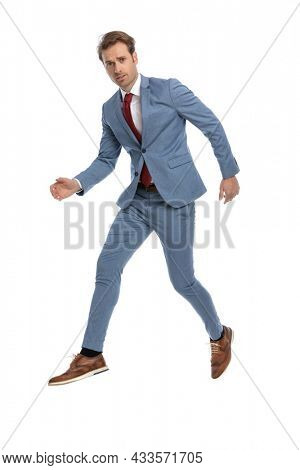 elegant young businessman in blue suit holding arms in fashion pose and jumping in the air on white background in studio, full body