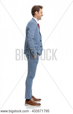side view of young man in blue suit holding hands in pockets, smiling and standing in line on white background in studio