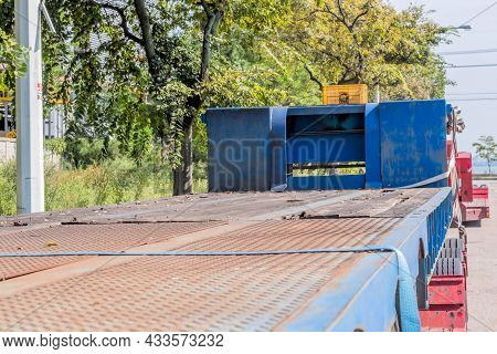 Two Flatbed Trailers Parked On Side Of Road In Urban Industrial Park.