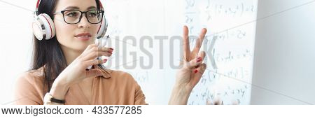 Portrait Of Female Teacher In Headphones Conducting Online Lesson Remotely