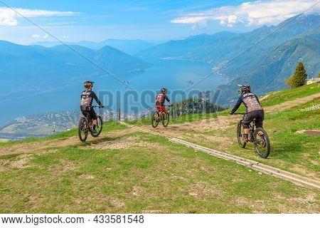 Verzasca, Switzerland - June 2021: Bikers By Mountain Bike Descending Down From Top Of Cardada-cimet