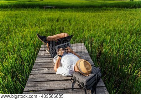 Top View Of Young Man Working, Using Laptop Computer In Nature. Freelance Work, Vacations, Distance