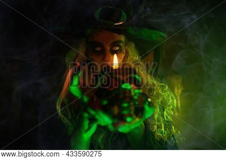Scary tales. A wicked ugly witch stands in an abandoned witch's den with a candle in her hands. Halloween.