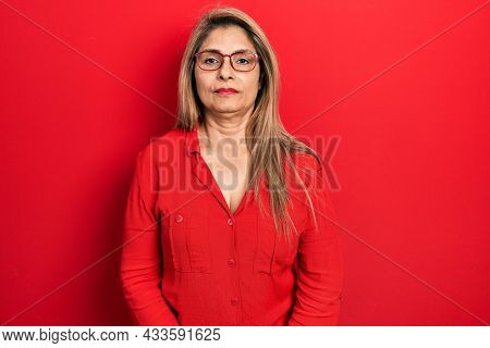 Middle age hispanic woman wearing casual clothes and glasses with serious expression on face. simple and natural looking at the camera.