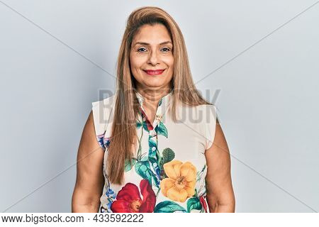 Middle age hispanic woman wearing casual clothes with serious expression on face. simple and natural looking at the camera.