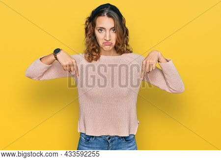 Beautiful young caucasian woman wearing casual sweater pointing down looking sad and upset, indicating direction with fingers, unhappy and depressed.
