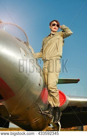 Military and commercial aircraft. Full length portrait of a confident pilot woman wearing uniform and sunglasses standing on her fighter jet ready to fly.