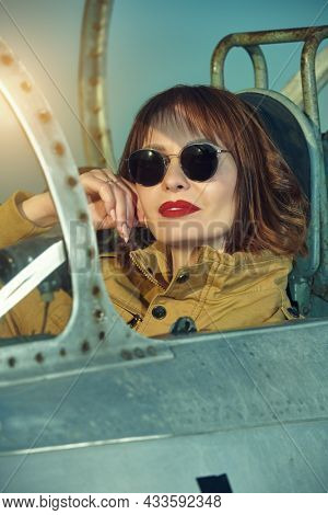 Portrait of a female pilot in the cockpit, wearing uniform and sunglasses. Civil and military aviation.