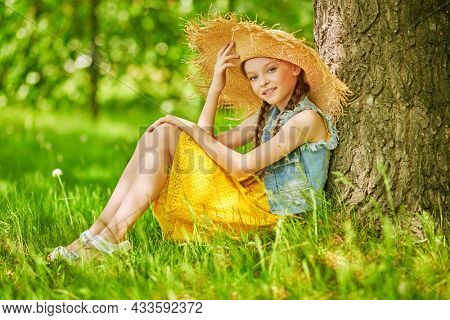 Full length portrait of a lovely girl in a wide-breamed straw hat having a rest under a tree in the park. Happy summer holidays.