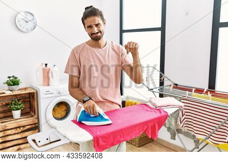 Young hispanic man ironing clothes at home pointing down looking sad and upset, indicating direction with fingers, unhappy and depressed.
