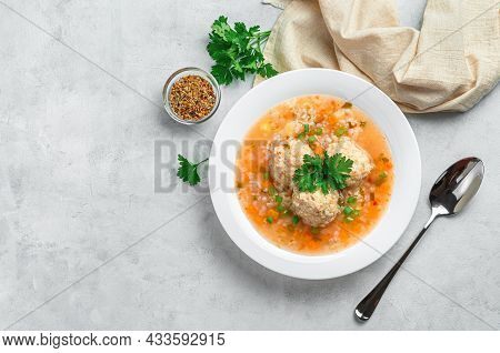 A Portion Of Soup With Meatballs, Rice And Vegetables On A Light, Gray Background.