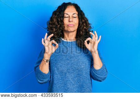 Middle age hispanic woman wearing casual clothes relax and smiling with eyes closed doing meditation gesture with fingers. yoga concept.