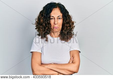 Middle age hispanic woman with arms crossed gesture depressed and worry for distress, crying angry and afraid. sad expression.