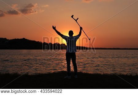 Man Raising Elbow Crutch Up To Sky Near River At Sunset, Back View. Healing Miracle