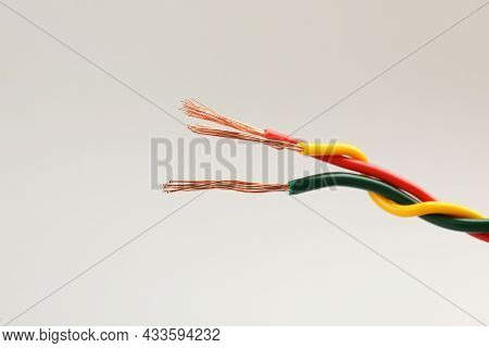 Three Twisted Electrical Wires On Light Background, Closeup