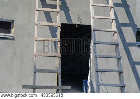 Two Wooden Stepladders Leaned Against A Gray Building. Plastered Building With An Empty Doorway And
