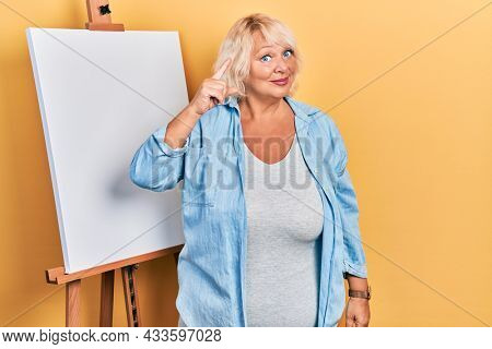 Middle age blonde woman standing by painter easel stand pointing finger up with successful idea. exited and happy. number one.