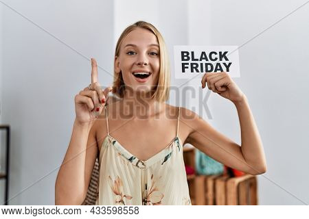 Young caucasian woman holding black friday banner at retail shop smiling with an idea or question pointing finger with happy face, number one