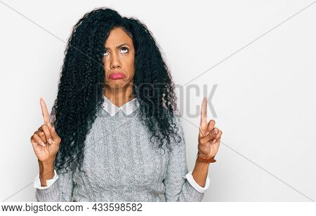 Middle age african american woman wearing casual clothes pointing up looking sad and upset, indicating direction with fingers, unhappy and depressed.
