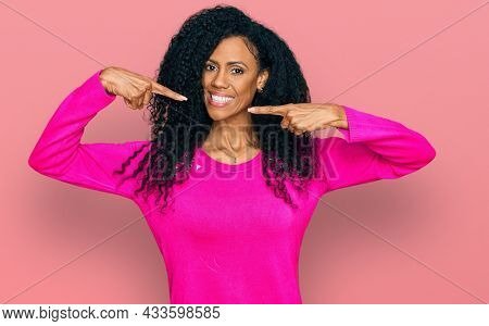 Middle age african american woman wearing casual clothes smiling cheerful showing and pointing with fingers teeth and mouth. dental health concept.