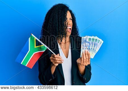 Middle age african american woman holding south african flag and rands angry and mad screaming frustrated and furious, shouting with anger. rage and aggressive concept.