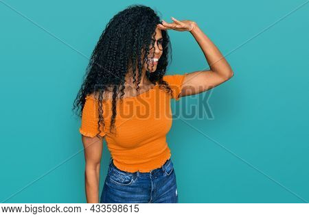 Middle age african american woman wearing casual clothes and glasses very happy and smiling looking far away with hand over head. searching concept.