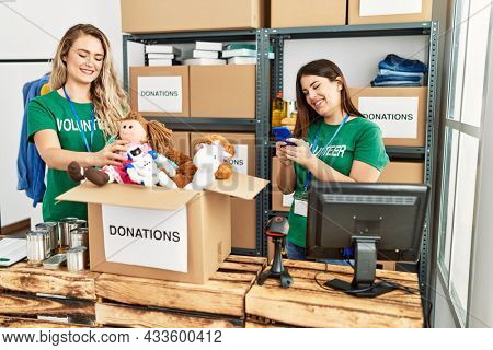 Two young volunteers woman smiling happy working at charity center. Girl smiling happy using smartphone.