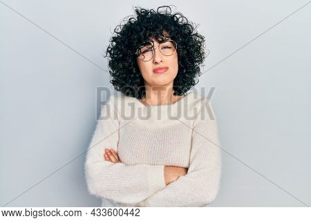 Young middle east woman with arms crossed gesture clueless and confused expression. doubt concept.