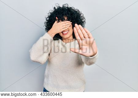 Young middle east woman wearing casual white tshirt covering eyes with hands and doing stop gesture with sad and fear expression. embarrassed and negative concept.