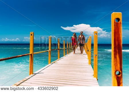 A Beautiful Couple Walks Along The Pier Of Paradise Island In Warm Sunny Weather. A Happy Couple Is