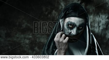 closeup of a scary evil nun, in a black and white habit, wearing a black face mask, in a panoramic format to use as web banner or header