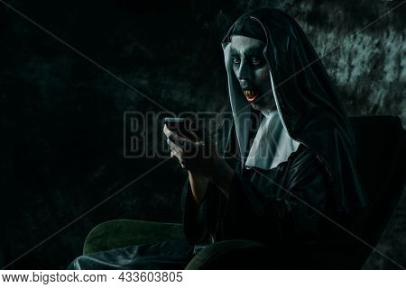 a scary evil nun, in a typical black and white habit, with bloody teeth, using her smartphone sitting in a chair
