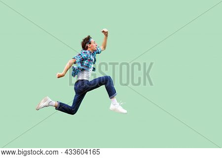Jump To The Success. Full Length Profile Side View Of Active Young Man In Casual Blue Checkered Shir